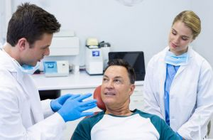 Dentist talking to patient with nurse watching - Oral Cancer Pinole, CA