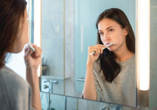 Woman brushing her teeth looking in mirror