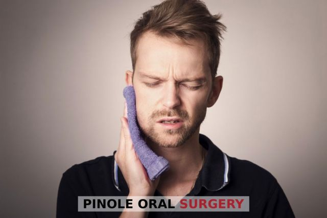 Man holding towel to his face in pain because of facial fractures - Pinole, CA