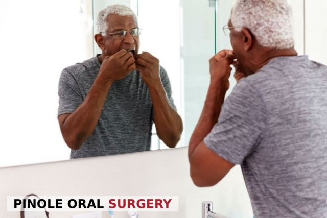 Senior African American man flossing his teeth correctly in front of a mirror - Pinole, CA